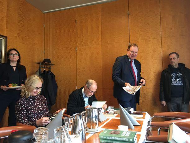 Paavo Lipponen saapui kirjanjulkistustilaisuuteen iltapäivälehdet kädessään. Rosila kirjoittaa pöydän päässä omistuskirjoitusta. Rosilan vieressä eduskunnan puhemiehenä 2015-2018 toiminut Maria Lohela.