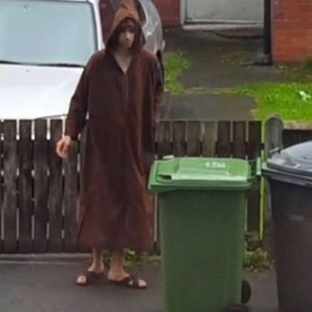 Ruskeaan kaapuun pukeutunut Salman Abedi tyhjentämässä roskista kotikadullaan Manchesterissa.