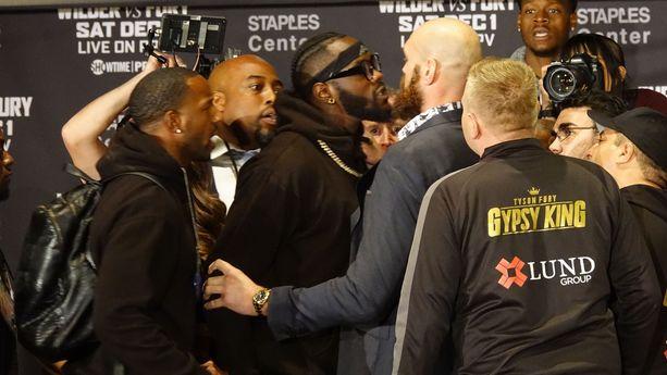 Tyson Fury (vaalea kalju) repi paitansa päältään yrittäessään psyykata Deontay Wilderia raskaan sarjan mestaruusottelun alla.
