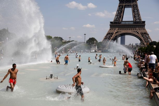 Ihmiset jäähdyttelevät Trocaderon suihkulähteissä Pariisissa.