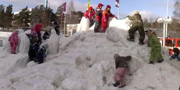 Lapset leikkivät lumilinnan harjalla.
