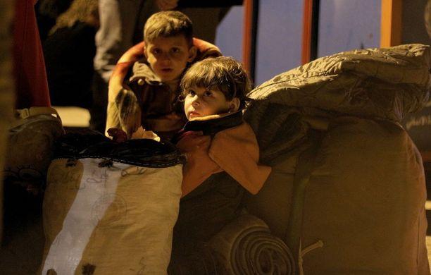Kaksi lasta lepäsi lauantaina saavuttuaan Al Ramousan alueelle Aleppossa Kefrayan ja Fuaan evakuoimisen jälkeen.