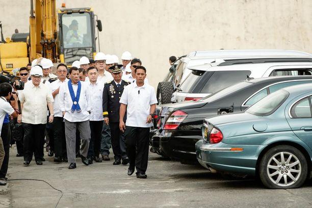 Presidentti Rodrigo Duterte (sininen kaulaliina) katseli autoja ennen niiden tuhoamista.