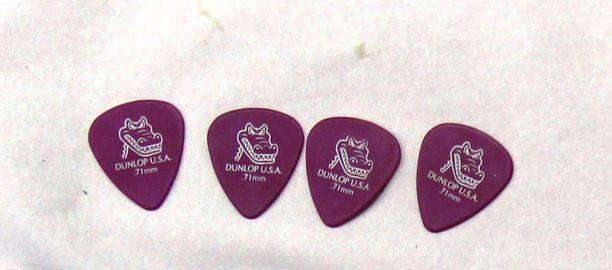 Mies saattoi olla kitaristi. Nämä plektrat löytyivät hänen lompakostaan muutaman kolikon kera.