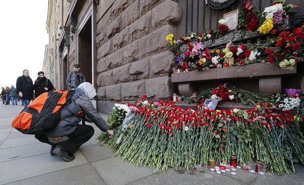 Pommi-iskun uhrien muistoksi on tuotu kukkia.