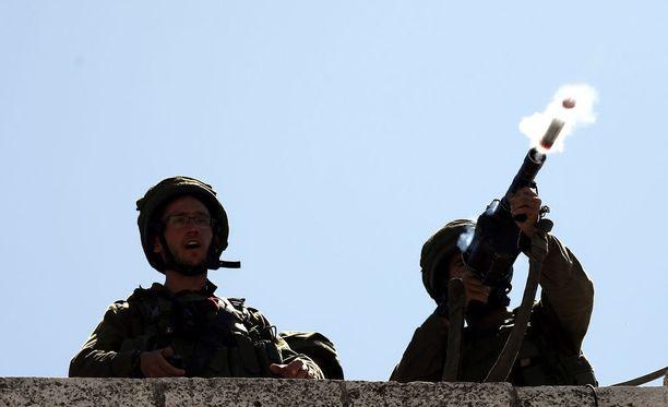 Israelin ja Palestiinan välillä levottomuudet ovat jälleen yltyneet. Kuvassa israelilaissotilas ampuu kyynelkaasukranaatin mellakoiden aikana Hebronissa.