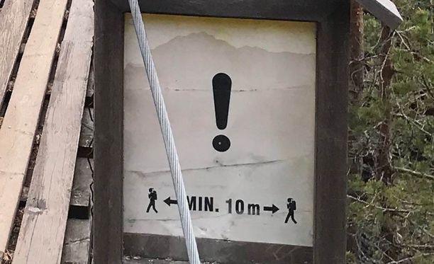 Varoituskyltti ohjeistaa kulkijoita riippusillalla.