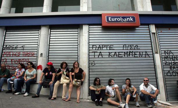 Huomisesta huolestuneet kreikkalaiset istuvat pankin edessä Ateenassa.