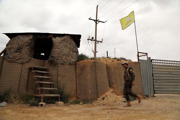 Kurditaistelija käveli tukikohdan ohi maaliskuussa. Kurdit ilmoittivat vallanneensa Isisin viimeisen linnakkeen 23. maaliskuuta 2019.