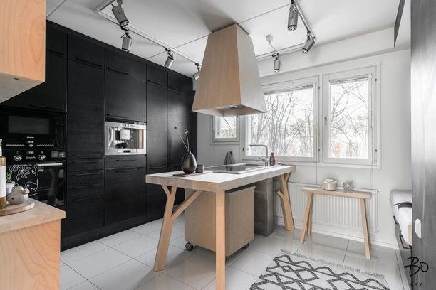 Mustat kaapistot ulottuvat lattiasta kattoon ja tunnelmaa on jälleen keventämässä vaalea puu ja valkoinen väri. Persoonallinen saareke on keittiön katseenvangitsija.