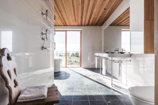 Kylpyhuonekin tuntuu sulautuvan osaksi ympäröivää luontoa muun muassa puisten yksityiskohtiensa kautta.
