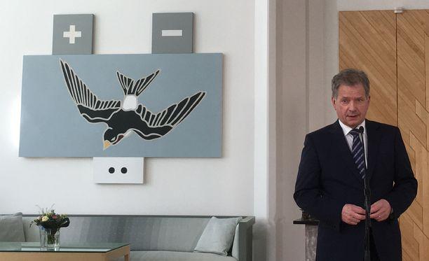 Presidentti Sauli Niinistö Osmo Rauhalan teoksen vieressä.