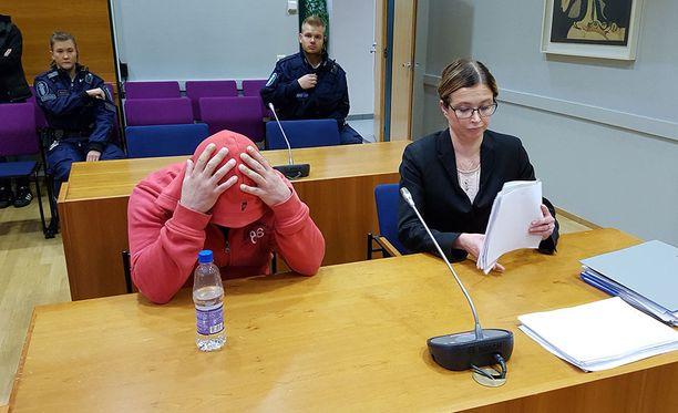 Taposta syytetty mies peitti kasvonsa oikeudessa.