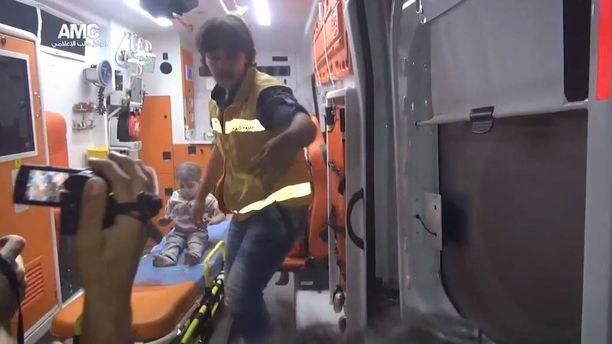 Pelastajat auttoivat Omranin ja tämän sisarukset ambulanssiin.