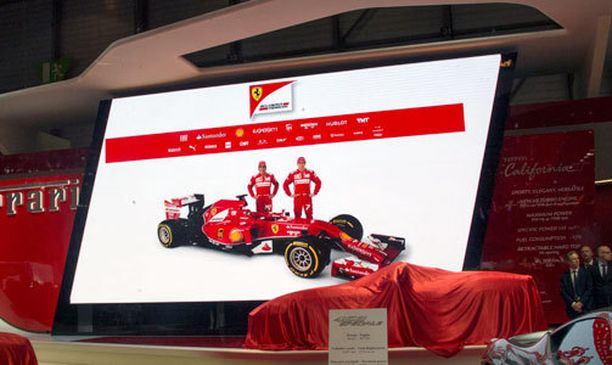 Mestarismiehet rinnakkain F1-autonsa edessä Ferrari-osaston isolla ruudulla.