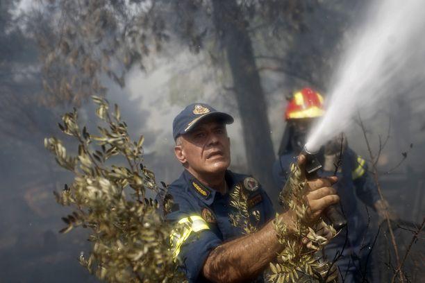 Pelastuslaitoksen varajohtaja Stefanos Kolokouris suihkutti vettä yrittäessään pelastaa maatilan lähellä Makrimallin kylää.