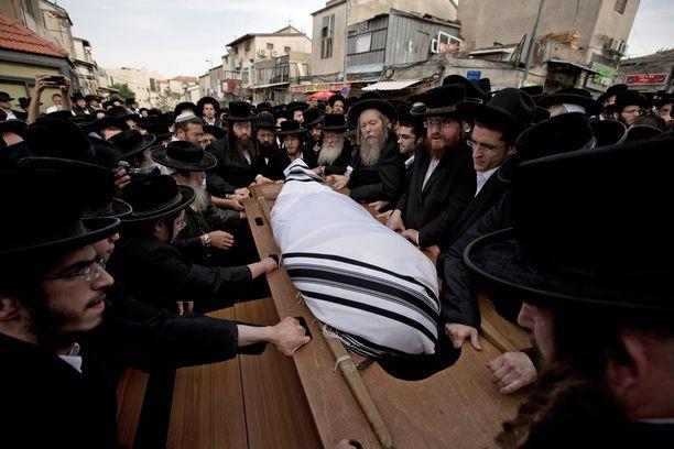 Ortodoksijuutalaiset kantavat 60-vuotiaan miehen ruumista. Yeshayahu Krishevsky kuoli tänään tiistaina, kun veitsihyökkääjä ajoi päin bussipysäkillä seisseitä ihmisiä.