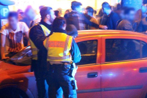 Poliisit taluttivat miestä pois tapahtumapaikalta Kölnissä. Poliisitehtävä tilanteen rauhoittamiseksi kesti aamuun asti.