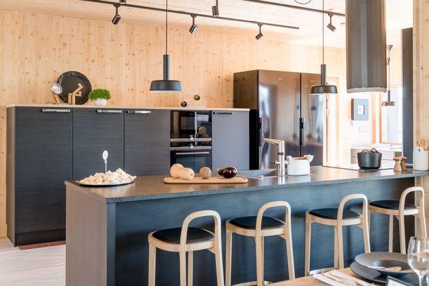 Puiset pinnat ja tuolit tekevät tästä keittiöstä hengittävän. Huomaa, että työtasot puuttuvat ja tilalla on korkeampi kaapisto, jonka yläpuolella on hengittävää tilaa.