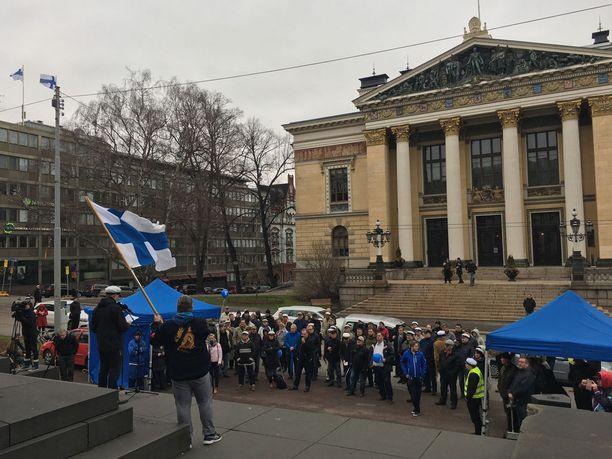 Halla-aho piti puheensa Snellmanin patsaan edessä. Perussuomalaisten pitkäaikainen aktiivi Raimo Mattson piteli Suomen lippua puheiden aikana.
