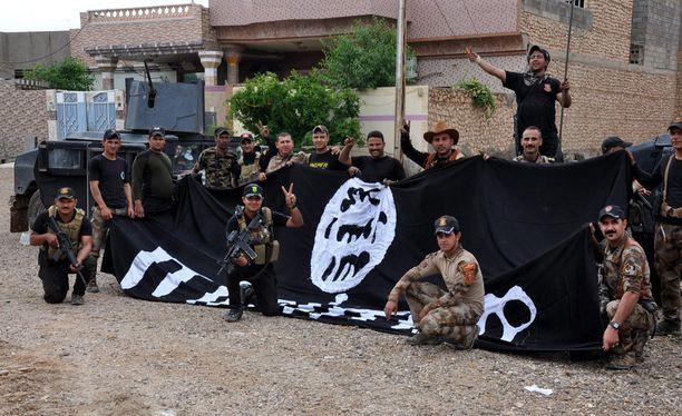 Irakilaiset sotilaat poseerasivat voitokkaina valtavan Isisin lipun edessä Hitissä. Irak sai kaupungin haltuunsa viime viikolla.