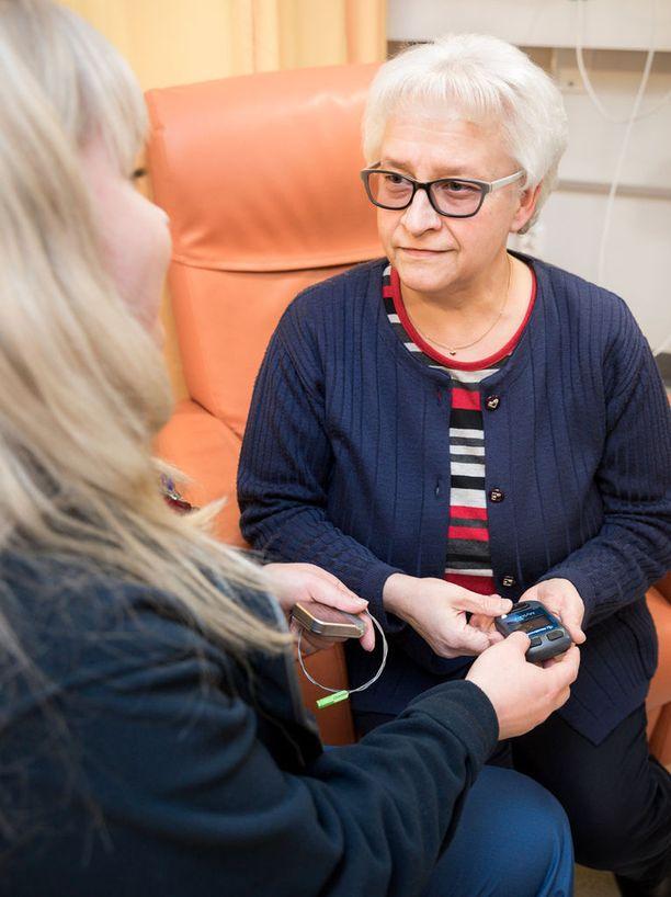 Merja Korhonen tutkii kipustimulaattorinsa voimakkuuden säätöjä sairaanhoitaja Heidi lauttasen kanssa.