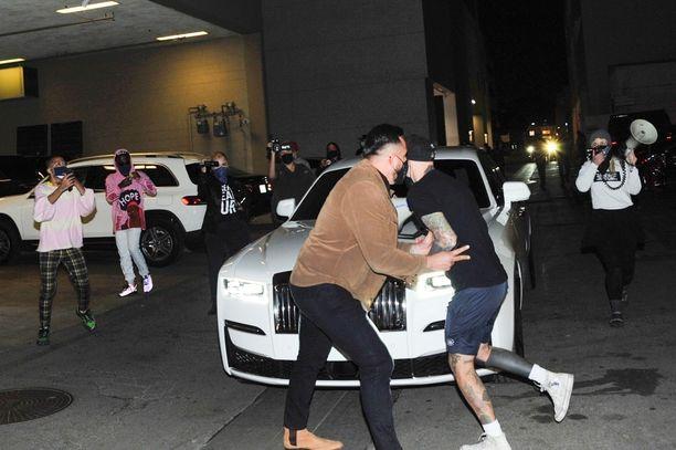 Aktivistit yrittivät estää Rolls-Roycen etenemisen. Jennerin turvamies ruskeassa takissa tuuppii yhtä aktivistia kauemmaksi.