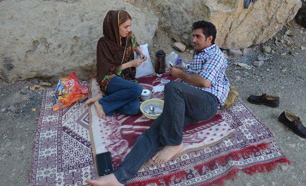 Pariskunta on asettunut kaupungin ulkopuolelle pelaamaan korttia ja nauttimaan piknikistä keskellä Ramadania.