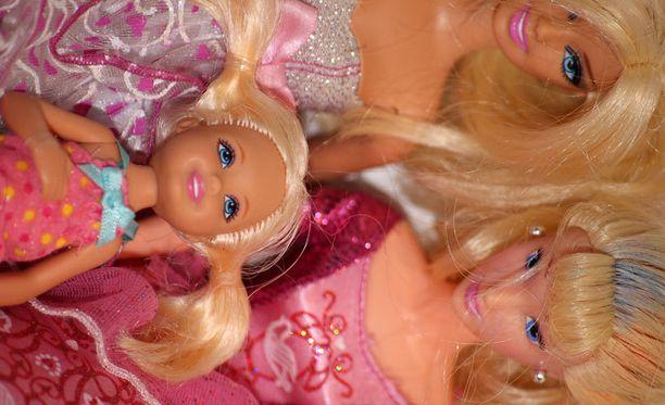 Monet askartelevat Barbie-nukeille vaatteita kotona.