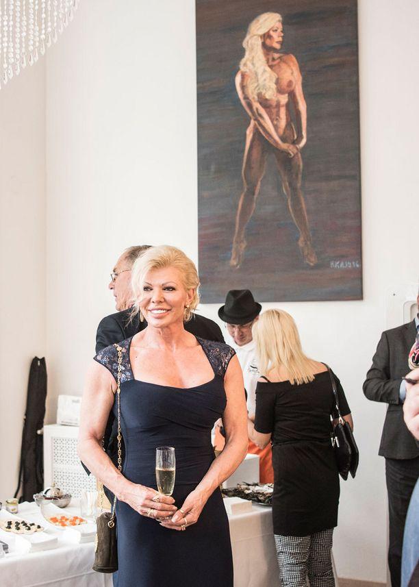 Kuvassa Tiina Jylhä-Valkonen poseeraa elokuussa hänestä tehdyn maalauksen kanssa.