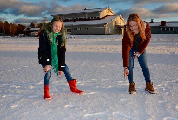Iina Viitala (vas.) ja Anni Pessinen näyttävät koulunsa pihamaalla olevia suden jälkiä. Takana näkyvän koulun vasemmalla puolella oleva punainen lampola lienee yksi syy siihen, miksi sudet viihtyvät Ihoden kylässä.