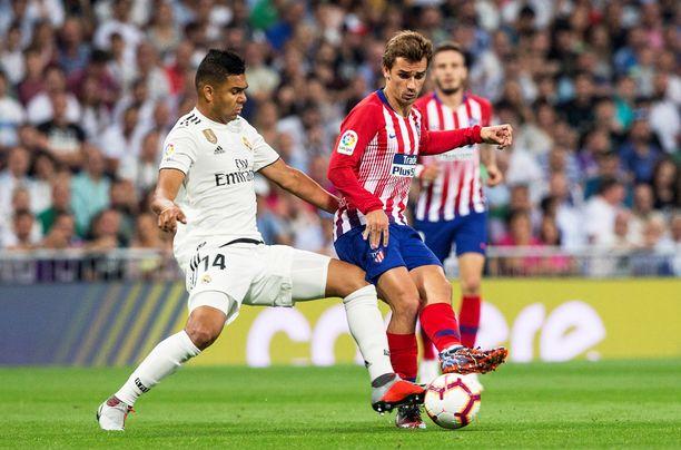 Real Madridin Casemiro (vas.) ja Atléticon Antoine Griezmann taistelivat pallosta Madridin paikallispelissä.