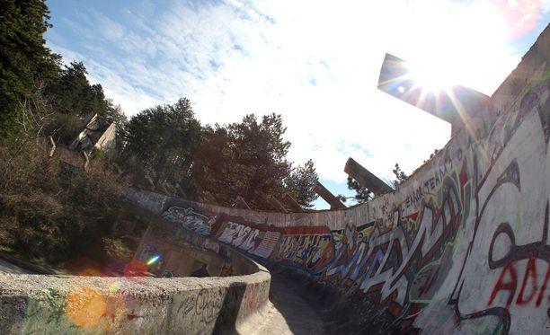 Sarajevon rattikelkkarataa koristavat graffitit. Radalle pääsee metsäpolkuja pitkin, ja nekin ovat kasvillisuuden peittämiä.