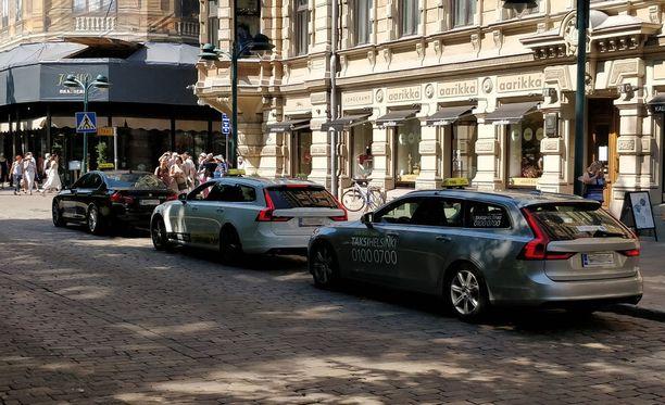 Esplanadin varrella taksitolpalle oli ryhmittynyt kaksi Taksi Helsingin ja yksi Lähitaksin auto.