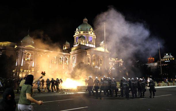 Poliisi otti yhteen mielenosoittajien kanssa tiistaina. Taustalla maan parlamentti.