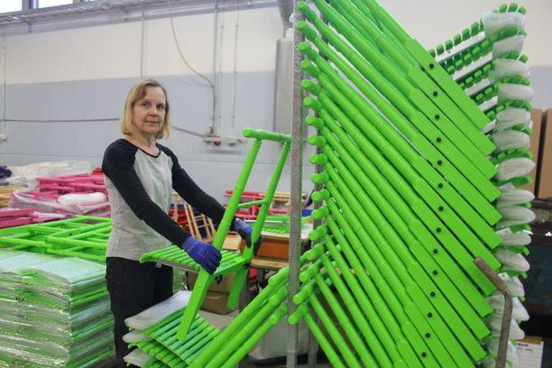 Tehtaalla työskentelevä Tarja Rajakorpi kiinnitti uuden värityksen saaneen kelkan istuimia ennen kelkan kokoonpanoa.