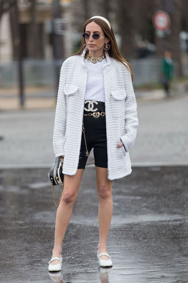 Loulou De Saison yhdistää trikoot valkoiseen t-paitaan ja pitkään jakkuun. Kasarihenkiset korut toimivat tässä asussa!