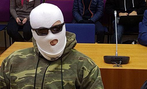 Syytetty peitti kasvonsa valkoisen kommandopipoa muistuttavan päähineen ja aurinkolasien avulla.