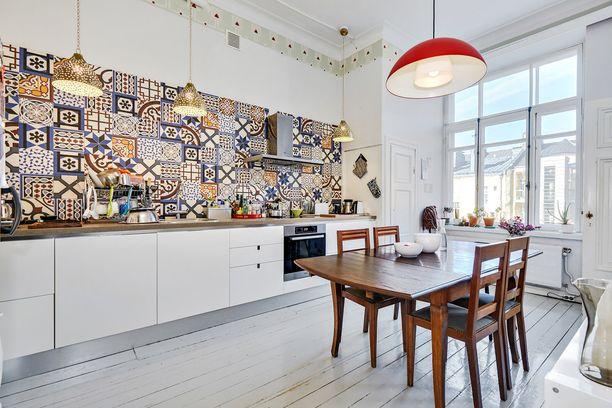 Värikäs laattaseinä vangitsee katseet valkoisessa keittiössä.