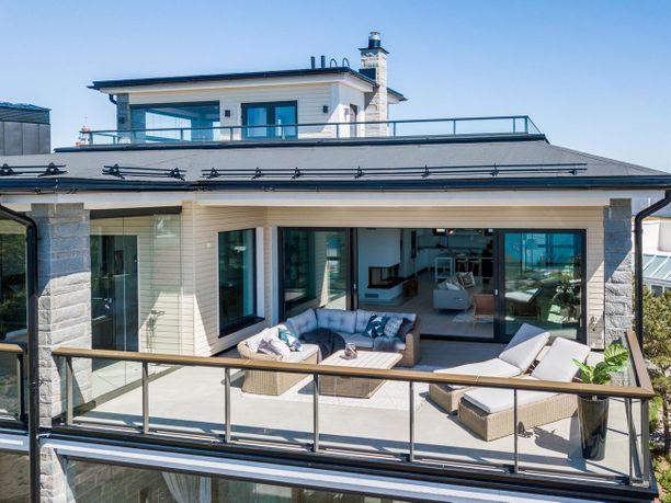 Kuvasta on hieman vaikea erottaa, mutta lasiovien takana on kattoterassin oma keittiö. Tämä penthouse sijaitsee Hangossa.