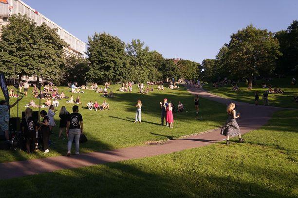Aurinko helli puistokaraokeen osallistuneita helsinkiläisiä.
