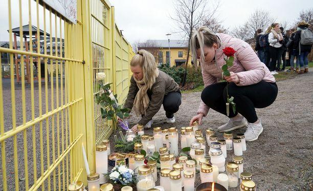 Lukiolaiset Meriliis Tamm ja Essi Nuutila toivat mustopaikalle ruusut ja kynttilät.