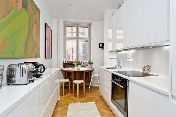 Keittiön välitilan lasiseinä on mukavaa vaihtelua laatoille. Lasi voi olla kirkasta, värillistä tai maalattua.