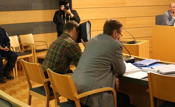 Kaksoissurmasta syytetty mies peitti kasvonsa oikeudessa.