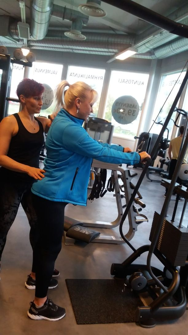 Kuvassa personal trainer Anne Manninen ohjeistaa Hanna Maariaa kuntosalilla.