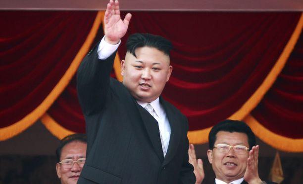 Kim Jong-un vilkutti kansalaisilleen korokkeelta, jonne oli kokoontunut myös hänen lähipiiriään.
