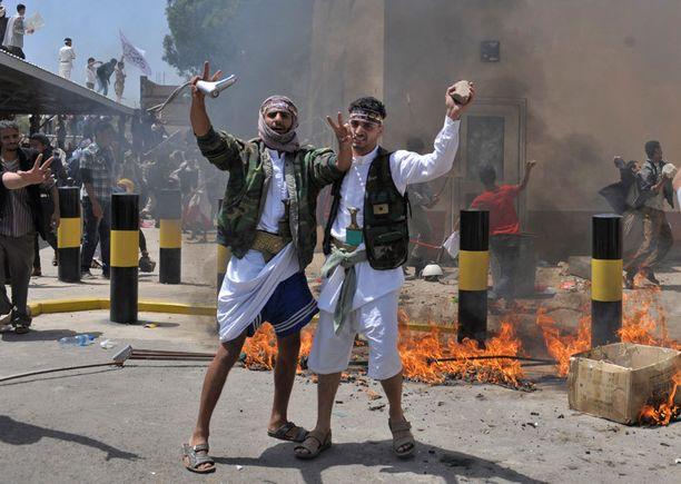 Jemenissä lähetystöön hyökänneet miehet juhlivat kadulla torstaina.