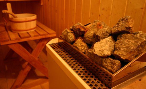 Naisen tyttären mukaan palvelukodin saunassa hoitajat säätelevät lämpöä painamalla napista löylyä kiukaalle. Kuvituskuva saunasta.