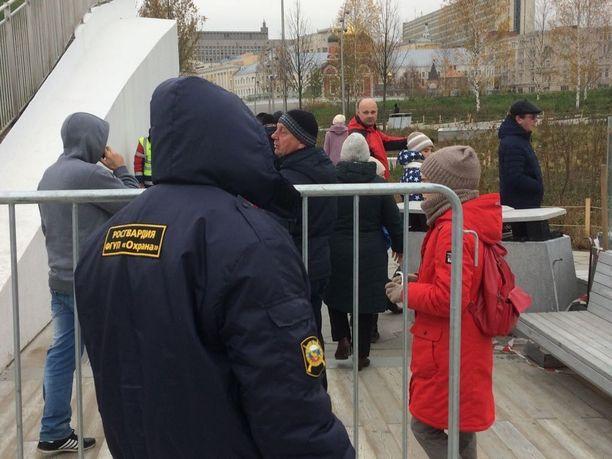 Kansalliskaartin turvallisuusmies ohjaa ihmisiä Kremlin lähistöllä Moskovassa.