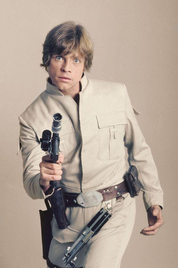 Mark Hamill Luke Skywalkerin rooliasussa. Valomiekka roikkuu vyöltä.